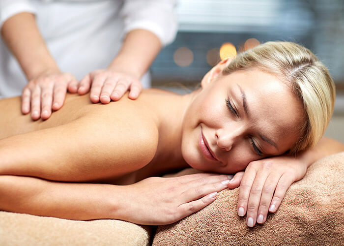 Woman enjoying a massage during a getaway in Marblehead, MA