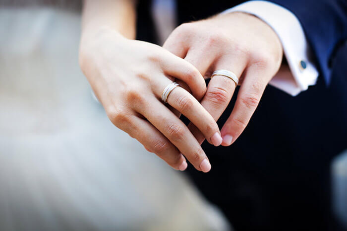 Close up of newly married couple's hands with rings on fingers