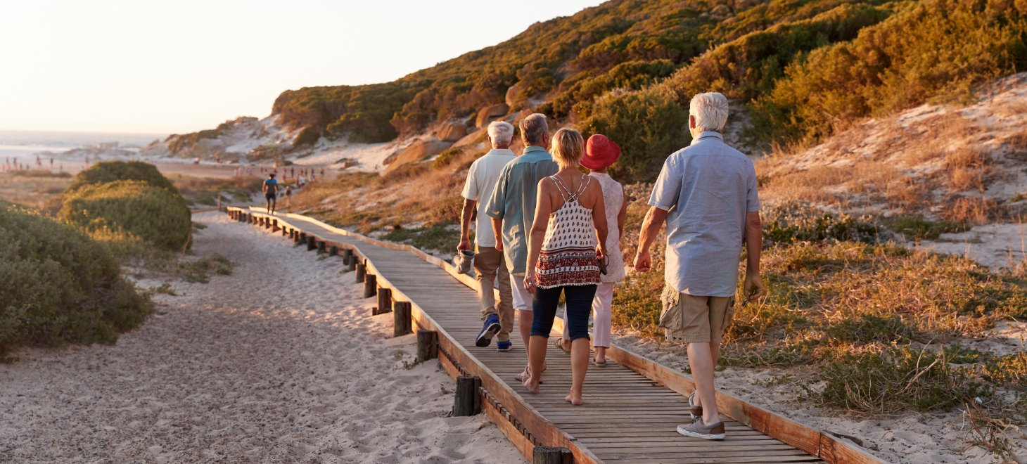 elderly group walking along beach boardwalk