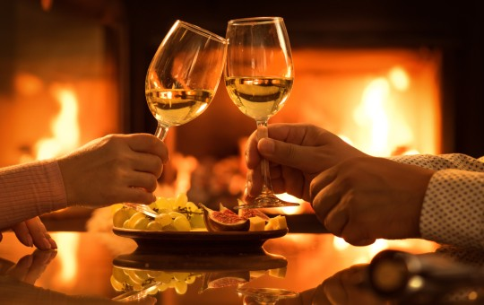couple toasting wine glasses by fireplace
